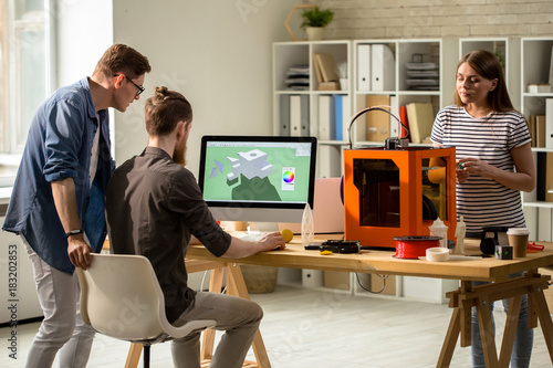 Back view portrait of young people working with 3D printer operating it via PC in modern design studio