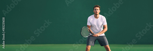 Tennis player man focused in ready position. A male athlete waiting for serve on panoramic green background banner. Challenge and concentration in competition.