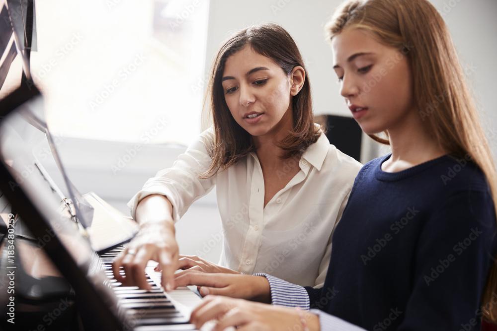 Kobieta uczeń z nauczycielem gry na pianinie w lekcji muzyki <span>plik: #183480259 | autor: Monkey Business</span>