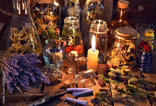 Bottles with herbs, lavender flowers, paper scrolls and magic objects on witch table. Occult, esoteric, divination and wicca concept. Mystic, old apothecary and vintage background