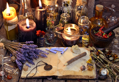 Open book with healing herbs, lavender flowers, candles, potion bottles and magic objects. Occult, esoteric, divination and wicca concept. Mystic, old apothecary and vintage background