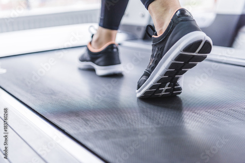 Fotografia cropped shot of woman in jogging sneakers running on treadmill