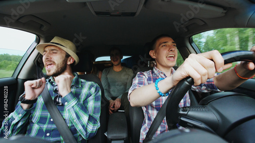Fotografia Group of happy friends in car singing and dancing while drive road trip