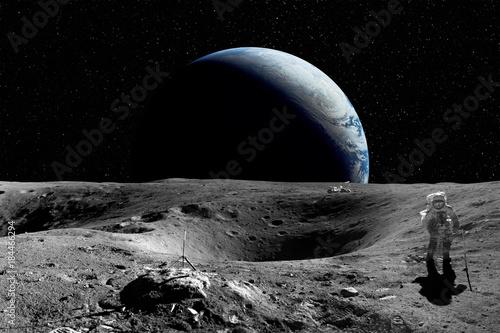 Fototapeta premium Astronauta na Księżycu. Planeta ziemia w tle. Elementy tego zdjęcia dostarczone przez NASA