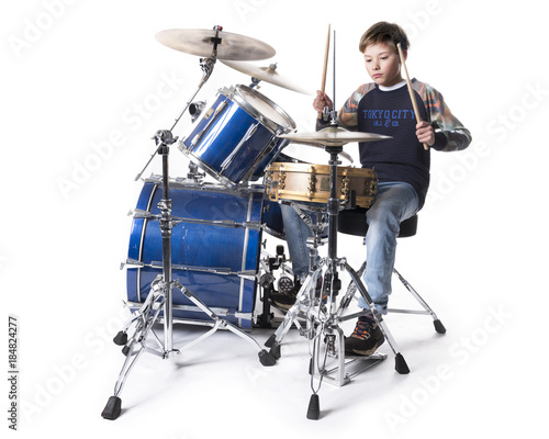 Carta da parati young blond boy at drum kit in studio against white background
