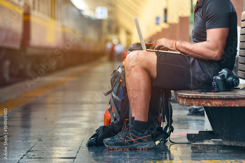 Fotografie, Obraz Tourist man with a backpack in the train station working on a laptop