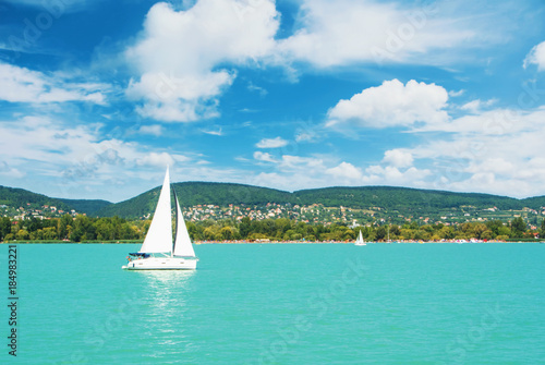 Fotografie, Obraz Panoramic view of lake river blue transparent water, a white sport modern luxury yacht sail boat floating and a green shore with forest, hills, villages and beach
