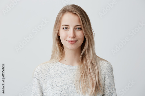 Pretty smiling joyfully female with fair hair, dressed casually, looking with satisfaction at camera, being happy Fototapeta