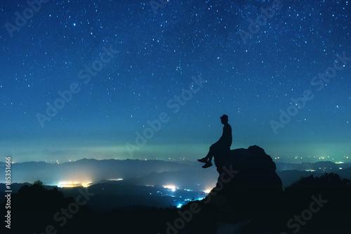 Stampa su Tela Man sits on big rock on night sky background