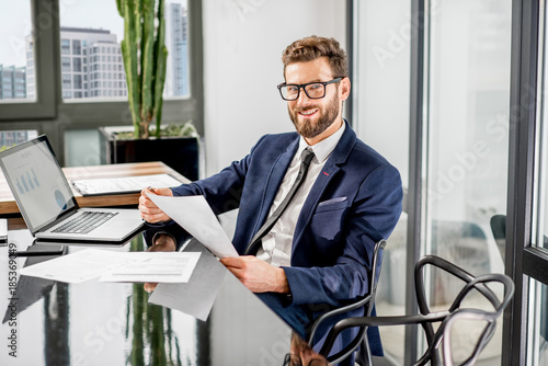 Portrait of a handsome banker working with laptop sitting at the luxury office i Fototapeta
