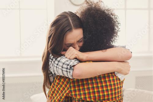Fotografie, Tablou Woman hugging her depressed friend at home