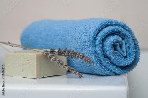 Slika na platnu Serviette de bain sur le rebord de baignoire avec savon à la lavande