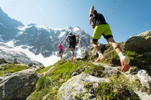 Fototapeta Three trail runners, two men and a woman, running up a steep trail in the mountains in the Alps on a hot, bright summer day