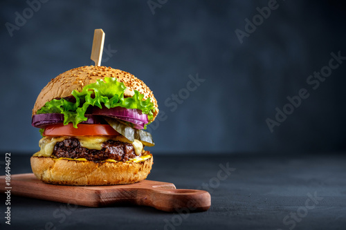 Fotografie, Tablou Tasty grilled beef burger with lettuce, cheese and onion served on cutting board on a black wooden table, with copyspace