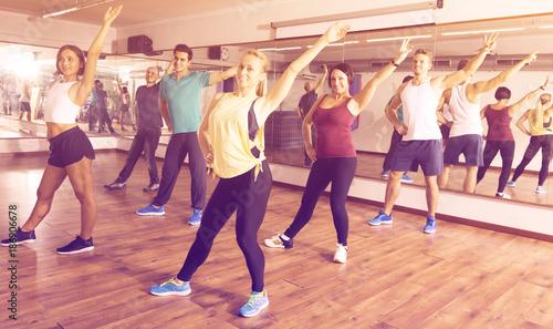 Obraz na plátne Happy people exercising zumba elements together