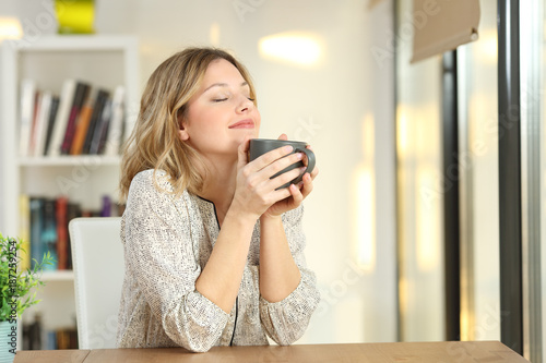 Woman breathing holding a coffee mug at home