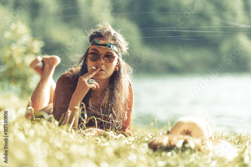 Pretty free hippie girl smoking on the grass - Vintage effect photo effect фототапет