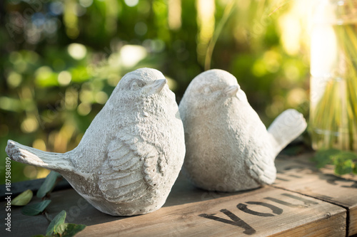 Statue couple birds in the garden.