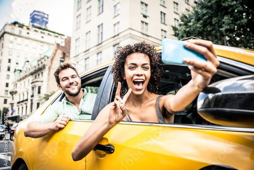 Fotografia, Obraz Happy couple on a yellow cab in New york
