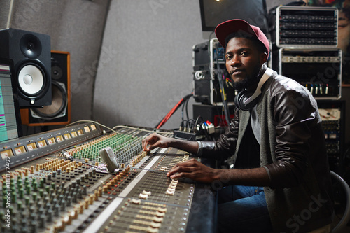 Modern young singer in rapper attire working in audio studio by recording equipment