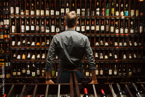 Bartender at wine cellar full of bottles with exquisite drinks