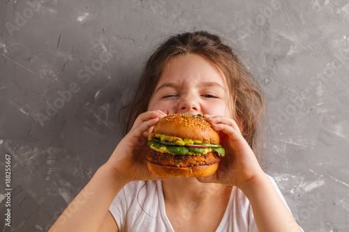 The little girl is eating a healthy baked sweet potato burger with a whole grains bun, guacamole, vegan mayonnaise and vegetables. Child vegan concept, gray background.