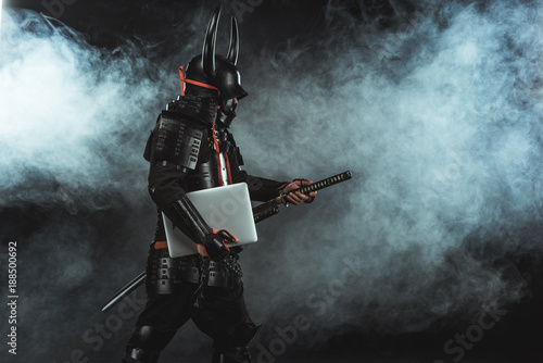 Stampa su Tela side view of samurai in traditional armor with laptop taking out sword on dark b