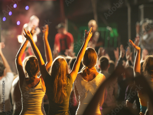Fotografija Audience with hands raised at a music festival and lights streaming down from above the stage