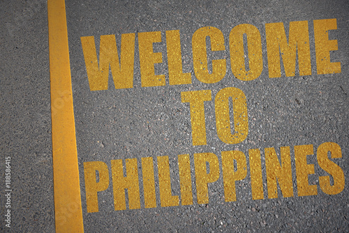 asphalt road with text welcome to philippines near yellow line. concept