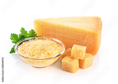Pieces of parmesan cheese and grated cheese in glass bowl isolated on white background.