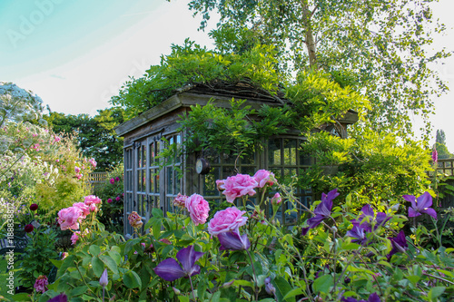 Summer house. in an English cottage garden, with rambling roses and clematis