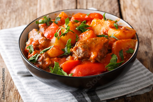 Slowly Stew beef with potatoes, carrots, peppers in spicy sauce in a bowl on the table. horizontal