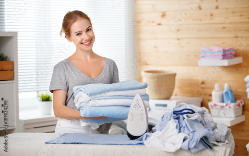 Fototapeta Happy woman housewife ironing clothes   in laundry at home