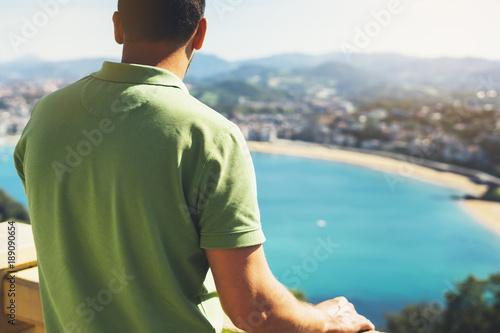 Fototapeta premium Hipster młody człowiek patrząc na taras widokowy podczas wakacji w San Sebastian, ciesząc się widokiem na morze na górze i oceanie, podróżnik turystyczny na tle panoramiczny widok na miasto