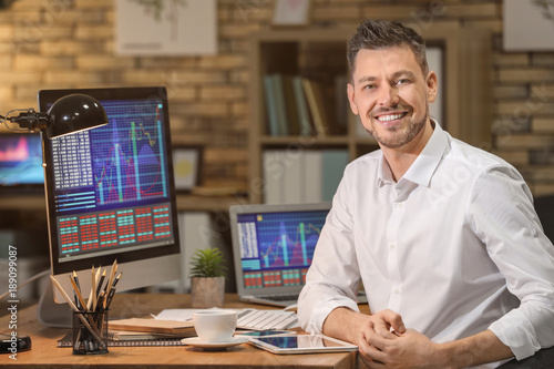 Fotografering Young stock exchange trader working in office