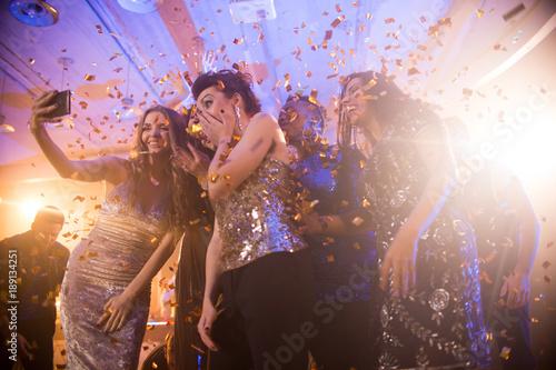 Group  of beautiful young women wearing glittering dresses dancing under golden Fototapeta