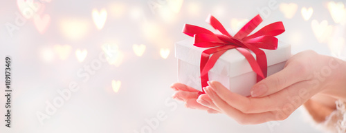 Valentine's Day. Woman holding gift box with red bow over holiday background