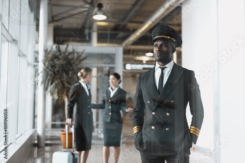 thoughtful young pilot in airport with stewardesses before flight Fototapeta