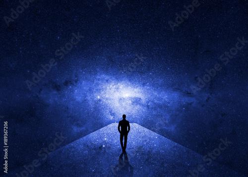 Fototapeta Man walking through the universe