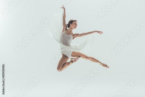 Wallpaper Mural young elegant ballerina in white dress jumping in studio, isolated on white