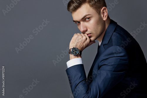 portrait of a man sitting with a suit with a watch, studio