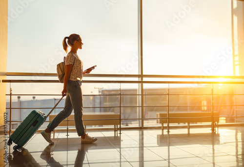 young woman goes at airport at window with suitcase waiting for plane