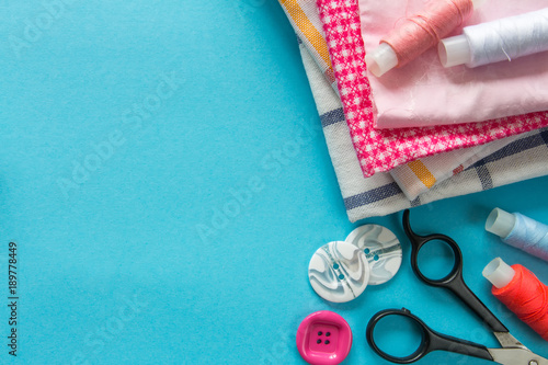 Fotografering Multicolored threads, scissors, buttons, fabric and various sewing accessories o
