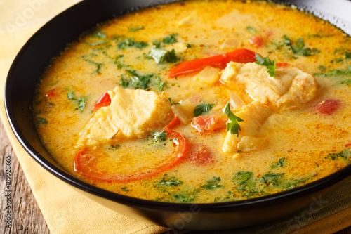 Brazilian fish Stew (Moqueca Baiana) with vegetables and coconut milk close-up on a plate. Horizontal