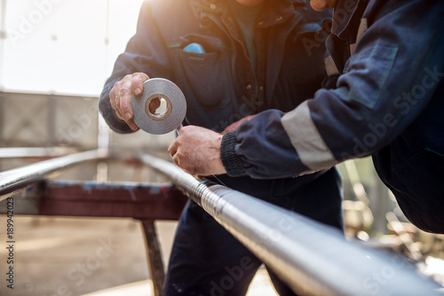Fotografía Focus hand view of professional industrial workers in uniform bonding metal pipe with duct tape