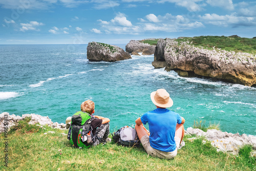 Father and son backpacker travelers rest on the rocky sea side and enjoy with beautiful view