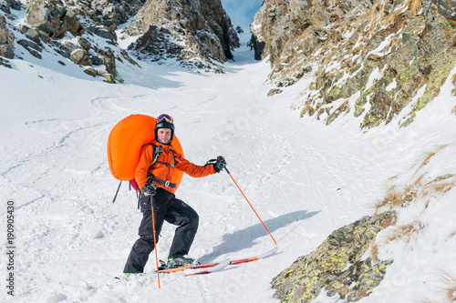 Foto Portrait of a smiling happy freeride backcountry skier with an opened avalanche dowel abs in a backpack