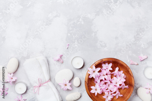 Spa, aromatherapy, beauty background with massage pebble, perfumed flowers water and candles on stone table top view. Relaxation and zen like concept. Flat lay.