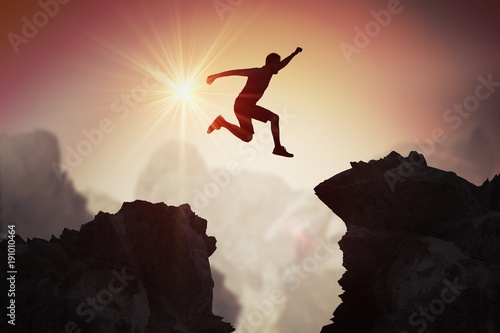 Fotografie, Obraz Silhouette of young man jumping over mountains and cliffs at sunset