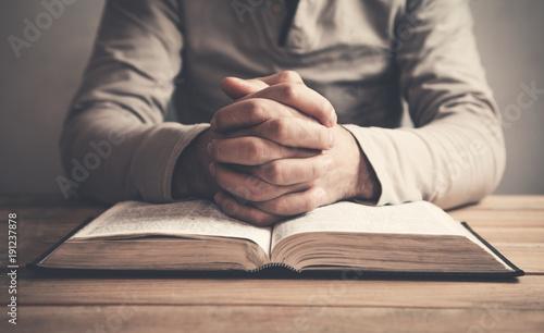 Man praying over a bible.